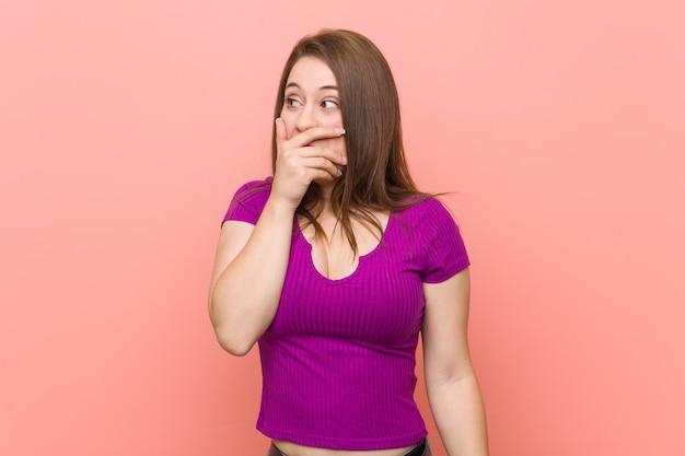 Junge hispanische frau gegen eine rosa wand, die zu einem copycovering mund mit der hand durchdacht schaut.