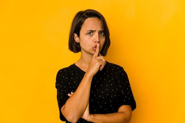 Junge hispanische frau isoliert auf gelb, ein geheimnis zu halten oder um stille zu bitten