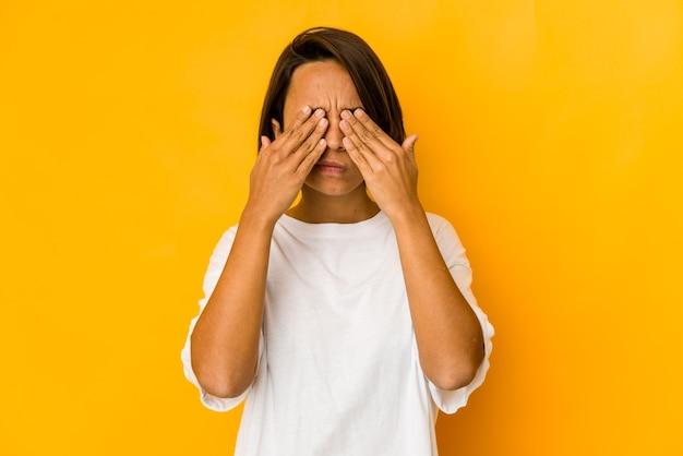 Junge hispanische frau isoliert auf gelb mit einem kopfschmerz, der vorderseite des gesichts berührt