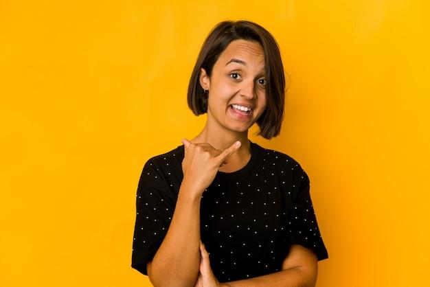 Junge hispanische frau isoliert auf gelbem lachen über etwas, mund mit händen bedeckend.