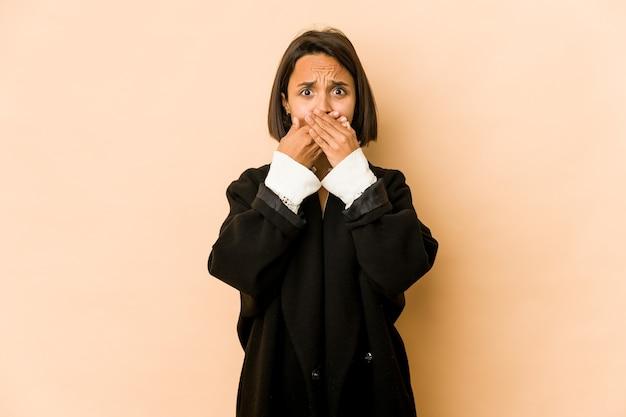 Junge hispanische frau isoliert bedeckte mund mit händen, die besorgt aussehen.