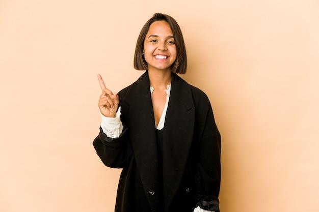 Junge hispanische frau isoliert zeigt nummer eins mit dem finger.