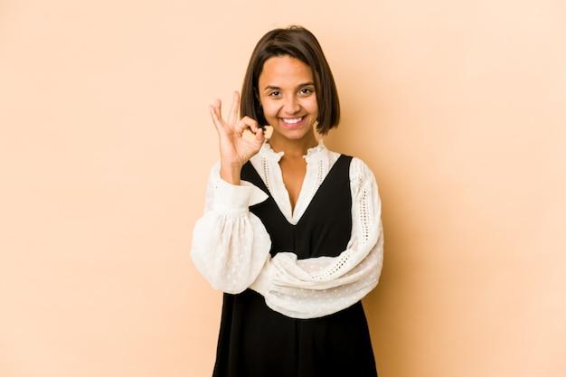 Junge hispanische frau isoliert zwinkert ein auge und hält eine okay geste mit der hand