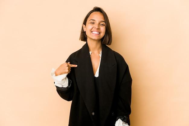 Junge hispanische frau isolierte person, die von hand auf einen hemdkopierraum zeigt, stolz und zuversichtlich
