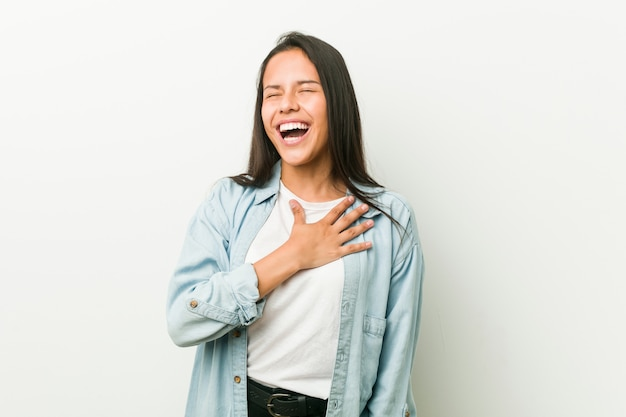 Junge hispanische frau lacht laut und hält die hand auf der brust.