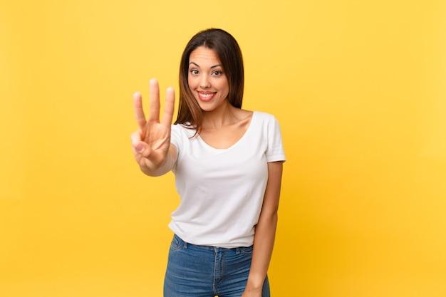 Junge hispanische frau lächelt und sieht freundlich aus und zeigt nummer drei