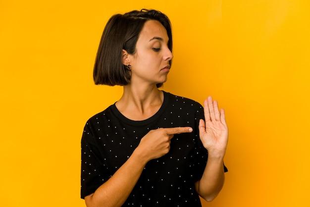 Junge hispanische frau lokalisiert auf gelbem lächelndem fröhlichem zeigen nummer fünf mit den fingern.