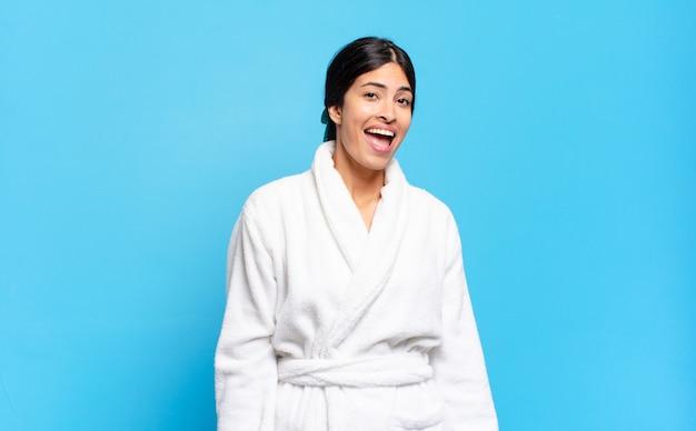 Junge hispanische frau mit einem großen, freundlichen, unbeschwerten lächeln, die positiv, entspannt und glücklich aussieht, chillig. bademantel-konzept
