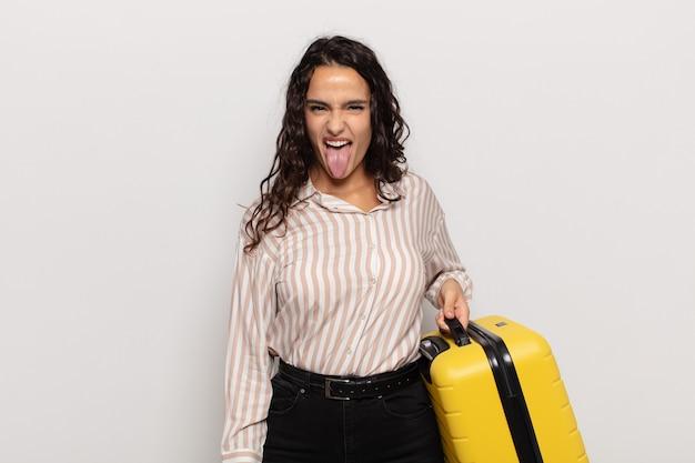Junge hispanische frau mit fröhlicher, sorgloser, rebellischer haltung, die scherzt und die zunge herausstreckt, spaß hat