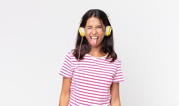Junge hispanische frau mit fröhlicher und rebellischer haltung, die scherzt und die zunge herausstreckt und musik mit kopfhörern hört