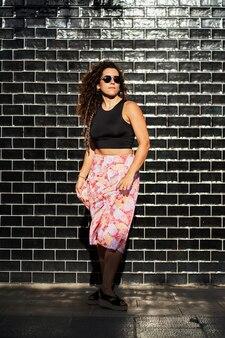 Junge hispanische frau mit sonnenbrille, die vor schwarzem ziegelsteinhintergrund posiert