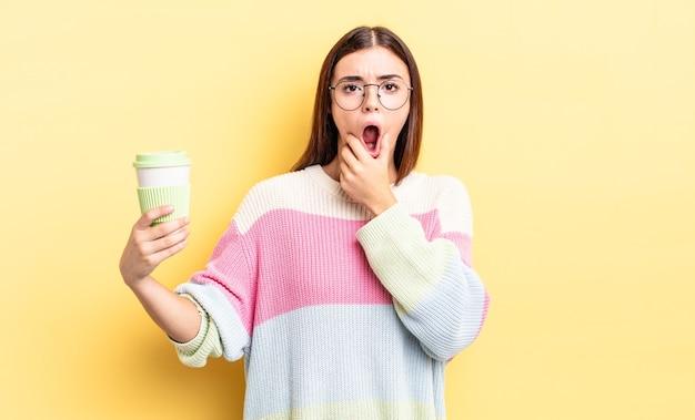 Junge hispanische frau mit weit geöffnetem mund und augen und hand am kinn. kaffee zum mitnehmen konzept