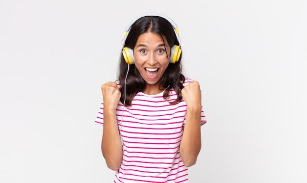 Junge hispanische frau schockiert, lacht und feiert erfolg beim musikhören mit kopfhörern