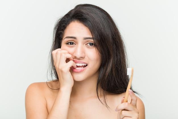 Junge hispanische frau, welche die beißenden fingernägel einer zahnbürste, nervös und sehr besorgt hält.