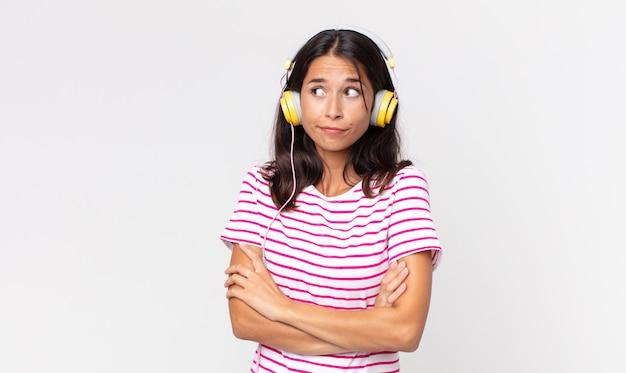 Junge hispanische frau zuckt mit den schultern, fühlt sich verwirrt und unsicher beim hören von musik mit kopfhörern