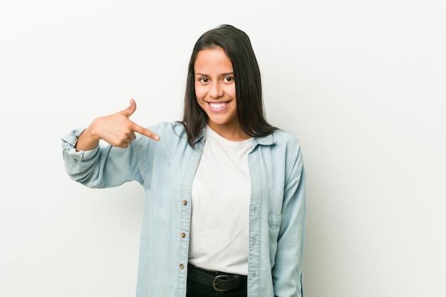 Junge hispanische frauenperson, die eigenhändig auf ein hemd, stolz und überzeugt zeigt
