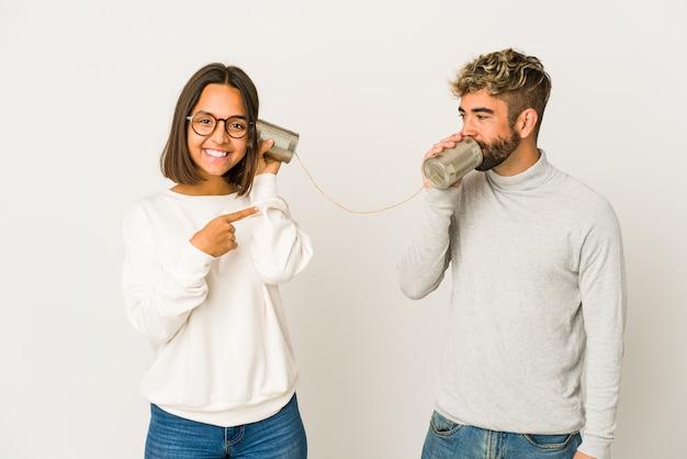 Junge hispanische freunde, die durch ein blechdosensystem sprechen, lächeln und zur seite zeigen und etwas an der leeren stelle zeigen.