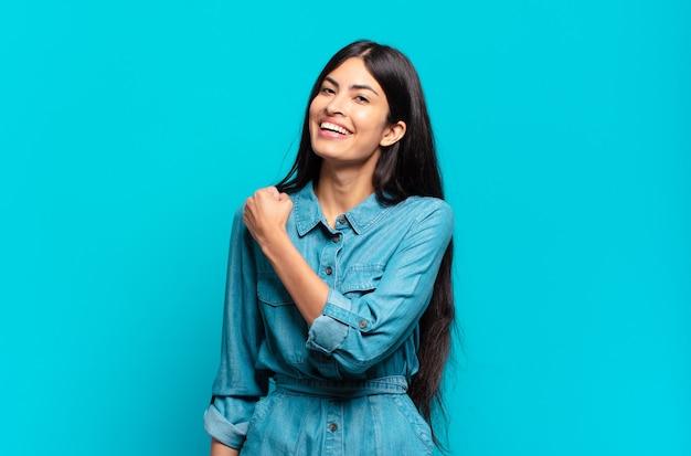 Junge hispanische gelegenheitsfrau, die sich glücklich, positiv und erfolgreich fühlt, motiviert, wenn sie sich einer herausforderung stellt oder gute ergebnisse feiert
