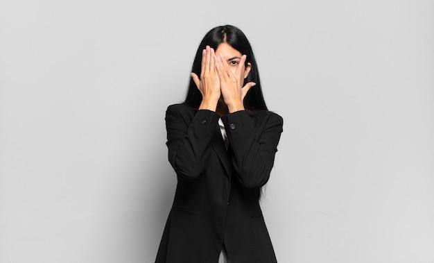 Junge hispanische geschäftsfrau, die das gesicht mit den händen bedeckt, zwischen den fingern mit überraschtem ausdruck späht und zur seite schaut