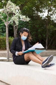 Junge hispanische geschäftsfrau, die draußen einige dokumente betrachtet. als präventivmaßnahme gegen das covid-19-virus trägt sie eine medizinische maske.