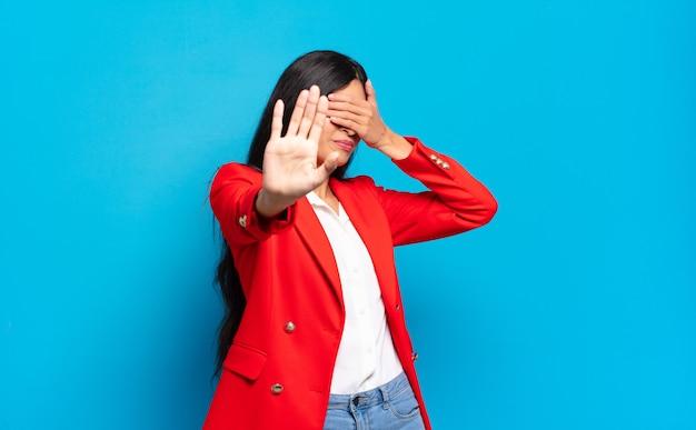 Junge hispanische geschäftsfrau, die gesicht mit hand bedeckt und andere hand nach vorne legt, um kamera zu stoppen, fotos oder bilder ablehnend
