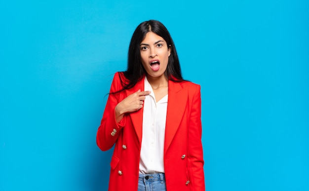 Junge hispanische geschäftsfrau, die schockiert und überrascht mit weit geöffnetem mund aussieht und auf sich selbst zeigt