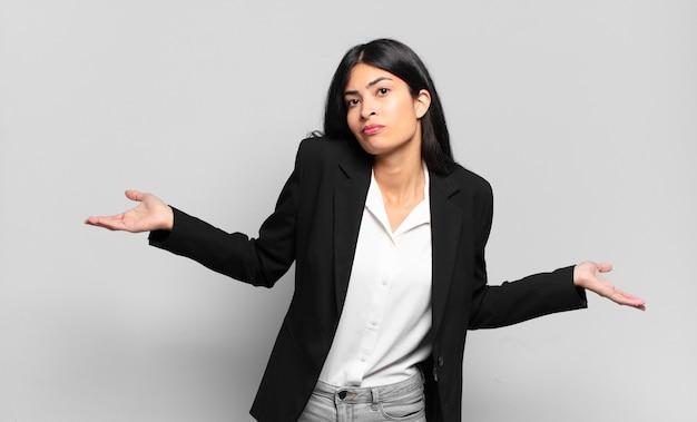 Junge hispanische geschäftsfrau, die sich ahnungslos und verwirrt fühlt, keine ahnung hat, absolut verwirrt mit einem dummen oder dummen blick