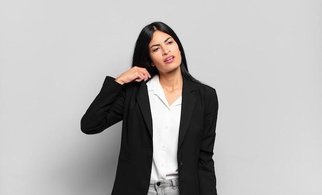 Junge hispanische geschäftsfrau, die sich gestresst, ängstlich, müde und frustriert fühlt, hemdhals zieht und mit problem frustriert aussieht