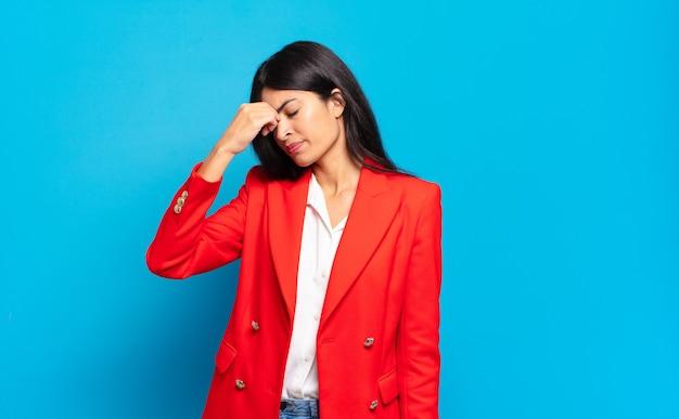 Junge hispanische geschäftsfrau, die sich gestresst, unglücklich und frustriert fühlt
