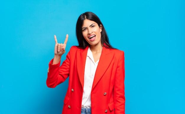 Junge hispanische geschäftsfrau, die sich glücklich, lustig, selbstbewusst, positiv und rebellisch fühlt und mit der hand rock- oder heavy-metal-schilder macht