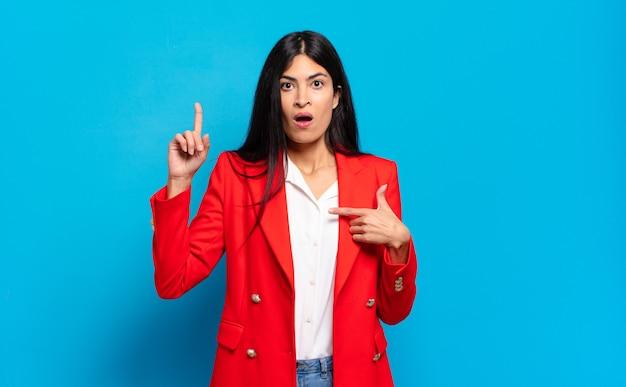 Junge hispanische geschäftsfrau, die stolz und überrascht ist, selbstbewusst zeigt und sich als erfolgreiche nummer eins fühlt