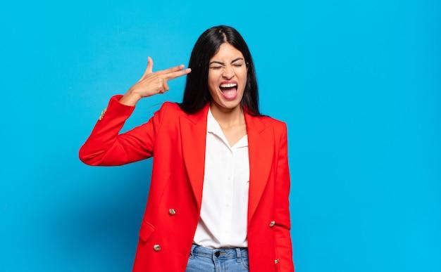 Junge hispanische geschäftsfrau, die unglücklich und gestresst aussieht, selbstmordgeste, die waffenzeichen mit der hand macht und auf kopf zeigt