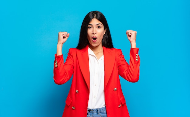 Junge hispanische geschäftsfrau, die wie ein gewinner einen unglaublichen erfolg feiert, aufgeregt aussieht und glücklich sagt, nimm das!