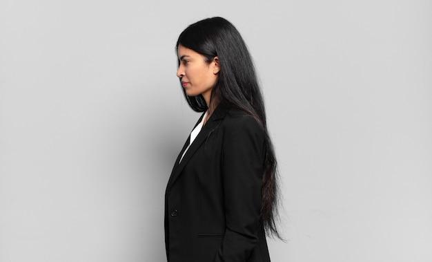 Junge hispanische geschäftsfrau in der profilansicht, die den raum nach vorne kopieren, nachdenken, sich vorstellen oder träumen möchte