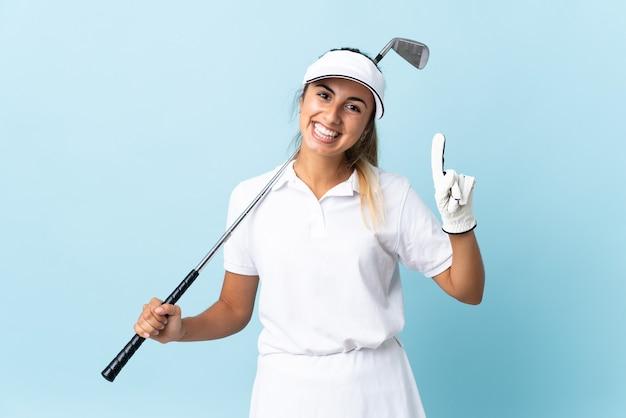 Junge hispanische golferin isolierte blaue wand, die einen finger im zeichen des besten zeigt und hebt
