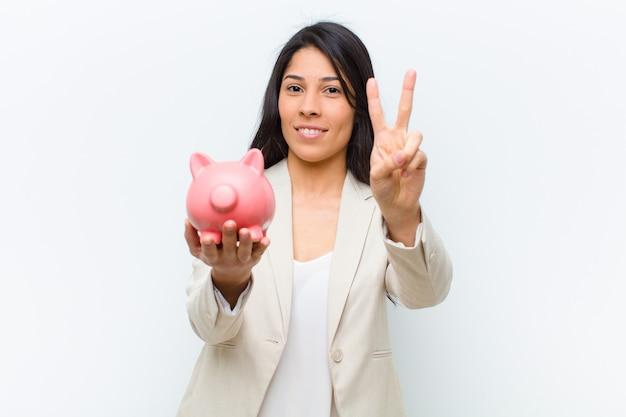 Junge hispanische hübsche frau mit einem sparschwein