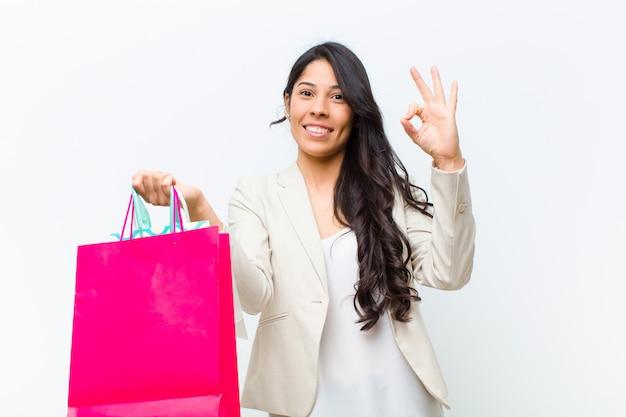 Junge hispanische hübsche frau mit einkaufstaschen