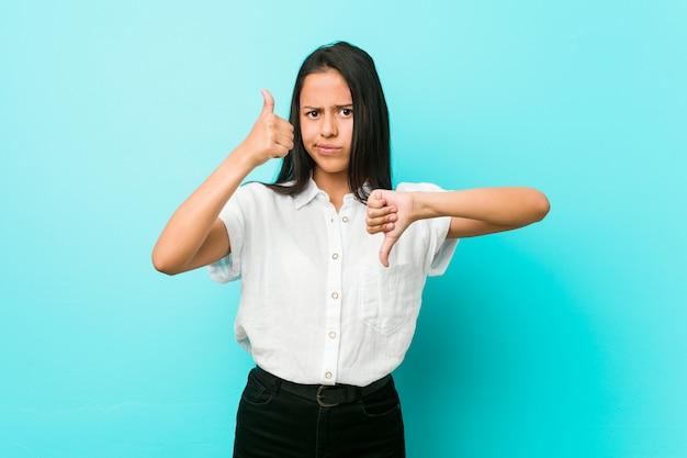 Junge hispanische kühle frau gegen eine blaue wand, die sich daumen und daumen unten zeigt, wählen schwierig konzept