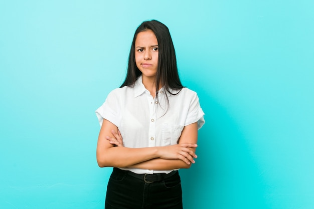 Junge hispanische kühle frau gegen eine blaue wand unglücklich, in camera schauend mit sarkastischem ausdruck.