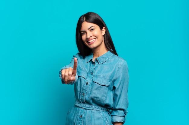 Junge hispanische lässige frau, die stolz und zuversichtlich lächelt und nummer eins triumphierend posiert und sich wie ein anführer fühlt