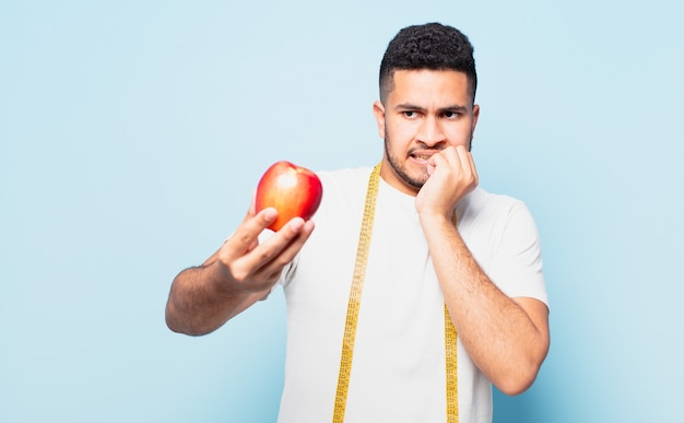 Junge hispanische mann erschrocken ausdruck und hält einen apfel. diätkonzept
