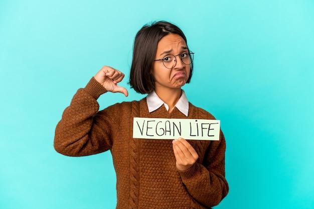 Junge hispanische mischlingsfrau, die ein veganes lebensplakat hält, fühlt sich stolz und selbstbewusst, beispiel zu folgen.