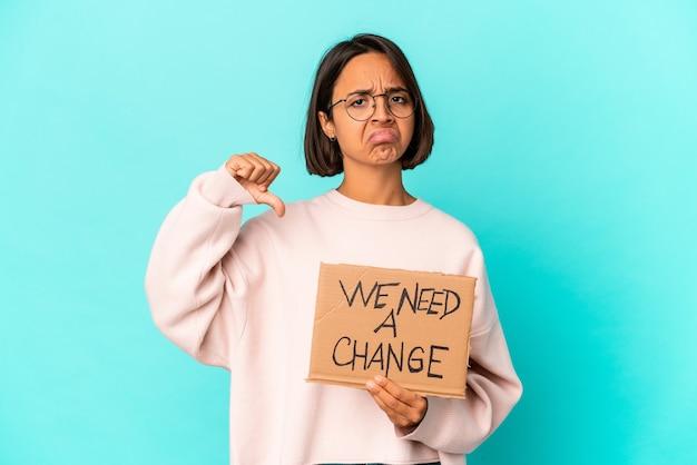 Junge hispanische mischlingsfrau, die eine inspirierende änderungsnachricht auf pappe hält, die eine abneigungsgeste zeigt, daumen nach unten. uneinigkeit konzept.