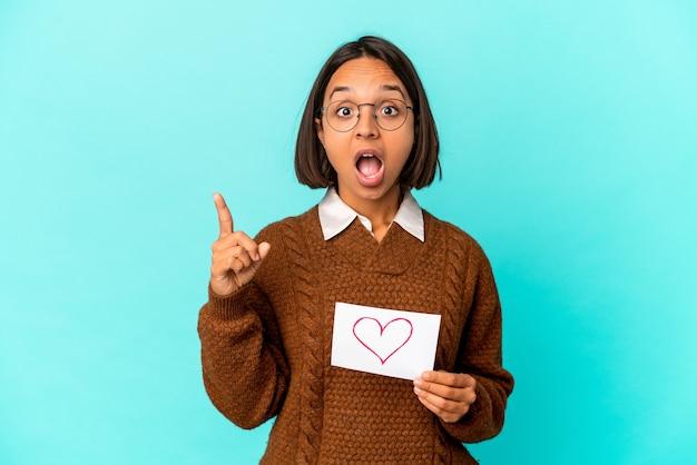 Junge hispanische mischrassenfrau, die ein herzpapier hält, das eine idee, inspirationskonzept hat.