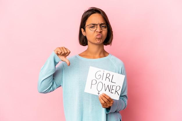 Junge hispanische mischrassenfrau, die ein mädchen-power-nachrichtenplakat hält, das eine abneigungsgeste zeigt, daumen nach unten. uneinigkeit konzept.