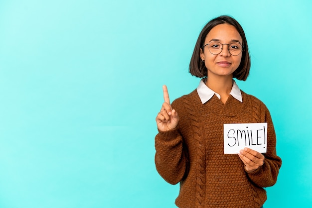 Junge hispanische mischrassenfrau, die eine lächelnnotiz hält, die nummer eins mit finger zeigt.