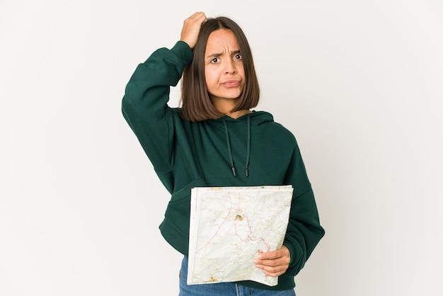 Junge hispanische reisende frau, die eine karte hält, die schockiert ist, sie hat sich an wichtiges treffen erinnert.