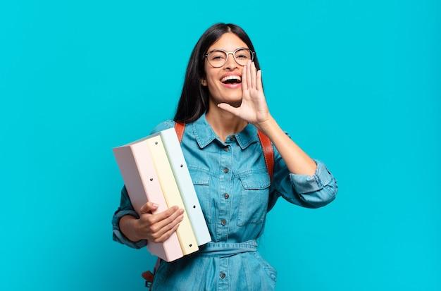 Junge hispanische studentin, die sich glücklich, aufgeregt und positiv fühlt und mit den händen neben dem mund einen großen schrei ausstößt