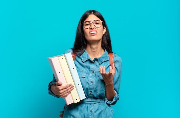 Junge hispanische studentin, die verzweifelt und frustriert, gestresst, unglücklich und genervt aussieht, schreit und schreit