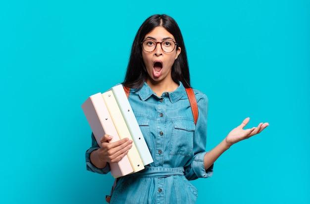 Junge hispanische studentin mit offenem mund und erstaunt, schockiert und erstaunt über eine unglaubliche überraschung
